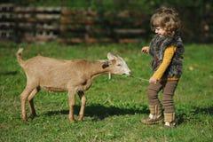 Małych dziewczynek sztuki z kózką na gospodarstwie rolnym Fotografia Stock