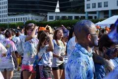 Mażący z barwionymi barwidłami, młodzi ludzie ma zabawę przy koloru Manila błyskotliwości bieg Fotografia Stock