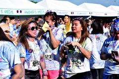 Mażący z barwionymi barwidłami, młodzi ludzie ma zabawę przy koloru Manila błyskotliwości bieg Zdjęcia Royalty Free