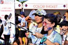Mażący z barwionymi barwidłami, młodzi ludzie ma zabawę przy koloru Manila błyskotliwości bieg Obrazy Royalty Free
