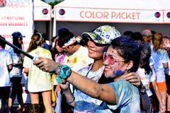 Mażący z barwionymi barwidłami, młodzi ludzie ma zabawę przy koloru Manila błyskotliwości bieg Fotografia Royalty Free