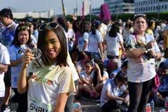 Mażący z barwionymi barwidłami, młodzi ludzie ma zabawę przy koloru Manila błyskotliwości bieg Obraz Stock