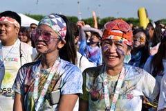 Mażący z barwionymi barwidłami, młodzi ludzie ma zabawę przy koloru Manila błyskotliwości bieg Obrazy Stock