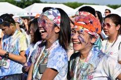 Mażący z barwionymi barwidłami, młodzi ludzie ma zabawę przy koloru Manila błyskotliwości bieg Obraz Royalty Free