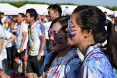 Mażący z barwionymi barwidłami, młodzi ludzie ma zabawę przy koloru Manila błyskotliwości bieg Zdjęcie Royalty Free