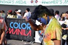 Mażący z barwionymi barwidłami, młodzi ludzie ma zabawę przy koloru Manila błyskotliwości bieg Zdjęcia Stock