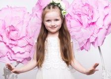 Mała czarodziejska dziewczyna w biel sukni na tle kwiaty Fotografia Stock