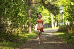 Mała dziewczynka bieg omija przez parka Obraz Stock
