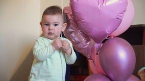 Ma?a dziewczynka chodzi pierwszych kroki na jej urodziny z ballons w domu, jeden rok zbiory