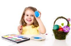 Mała dziewczynka dekoruje tradycyjnego Wielkanocnego jajko Obraz Royalty Free