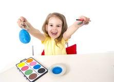 Mała dziewczynka dekoruje tradycyjnego Wielkanocnego jajko Fotografia Stock