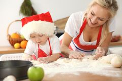 Ma?a dziewczynka i jej blondynki mama w czerwonych fartuchach bawi? si? i ?mia si? podczas gdy ugniataj?cy ciasto w kuchni domowe zdjęcia stock