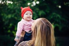 Mała dziewczynka i jej macierzysty odprowadzenie w parku Czerwony kapelusz niebieskie oczy zdjęcia stock