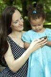 Mała dziewczynka i jej matka na telefonie Fotografia Royalty Free