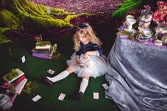 Mała dziewczynka jako Alice w krainy cudów dolewania herbacie Zdjęcia Royalty Free
