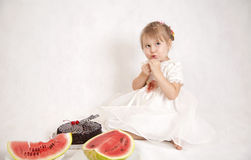 Mała dziewczynka je arbuza i tort Zdjęcie Royalty Free