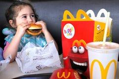 Mała dziewczynka je fast food Zdjęcia Royalty Free