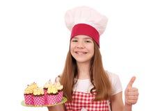 Mała dziewczynka kucharz z muffins up i kciukiem Fotografia Stock