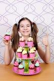 Mała dziewczynka kucharz z muffins up i kciukiem Zdjęcia Royalty Free
