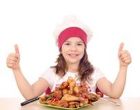 Mała dziewczynka kucharz z piec kurczaków kciukami i drumstick Obrazy Stock