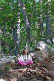 Mała dziewczynka medytuje w lesie Obrazy Royalty Free