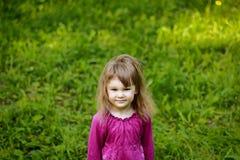 Mała dziewczynka na zielonej trawie Obrazy Royalty Free