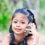 Mała dziewczynka opowiada na telefonie. Zdjęcia Royalty Free