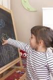 Mała dziewczynka punkt przy jej rysunkiem kwiaty na blackboard Zdjęcie Stock
