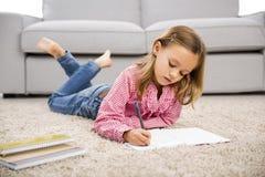 Mała dziewczynka robi pracie domowej Zdjęcia Stock