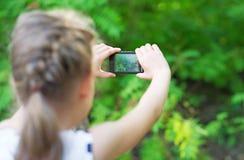 Mała dziewczynka robi wideo lub fotografii Fotografia Stock
