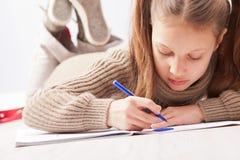 Mała dziewczynka rysunek na jej notatniku Obrazy Royalty Free