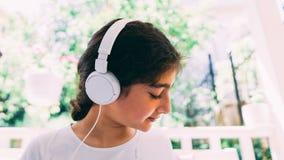 Ma?a dziewczynka s?ucha muzyka, cieszy si? melodi? na kanapie zdjęcia royalty free
