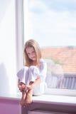 Mała dziewczynka siedzi blisko okno Zdjęcia Stock