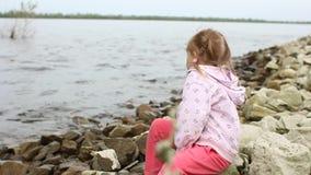 Mała dziewczynka siedzi na brzeg rzeki zbiory