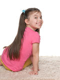 Mała dziewczynka siedzi na dywanie i patrzeje z powrotem Obraz Stock