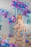 Mała dziewczynka siedzi na schodki w studiu z mnóstwo kolorów balonami Zdjęcie Royalty Free