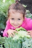 Mała dziewczynka siedzi w kapuscie w ogródzie Fotografia Royalty Free
