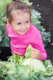 Mała dziewczynka siedzi w kapuscie w ogródzie Zdjęcie Royalty Free