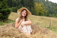 Mała dziewczynka siedzi w siano wsi lata seaso Fotografia Stock