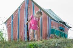 Mała dziewczynka stoi blisko pasiastego rocznika campingowego namiotu brezentowego Fotografia Stock