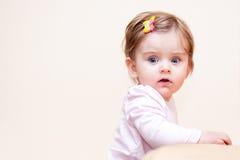 Mała dziewczynka stojaki blisko kanapy w domu Zdjęcia Stock