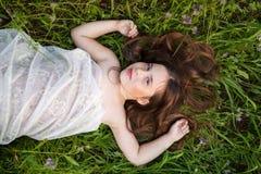 Mała dziewczynka w biel sukni lying on the beach w trawie Zdjęcia Royalty Free