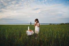 Mała dziewczynka w bielu smokingowym pije mleku w zieleni polu Lato równo Zdjęcie Royalty Free