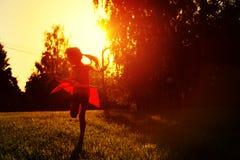 Mała dziewczynka w czerwonym smokingowym tanu w zmierzchu Zdjęcie Stock