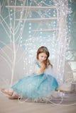 Mała dziewczynka w eleganckiej sukni obsiadaniu na saniu Obrazy Stock