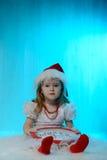 Mała dziewczynka w Santa kapeluszu z zegarem Zdjęcie Royalty Free