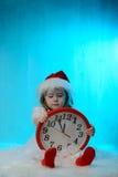 Mała dziewczynka w Santa kapeluszu z zegarem Obraz Stock