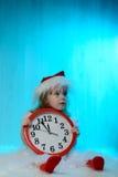 Mała dziewczynka w Santa kapeluszu z zegarem Zdjęcie Stock