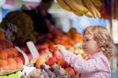 Mała dziewczynka wybiera owoc w rynku Fotografia Royalty Free