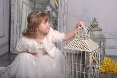Ma?a dziewczynka z biel sukni? blisko kom?rki z kwiatami zdjęcie stock
